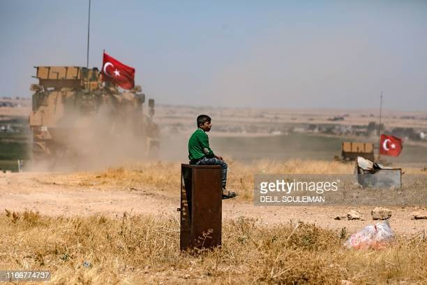 Boy watches a Turkish military convoy drive past in the Syrian village of al-Hashisha on the outskirts of Tal Abyad town along the border with...