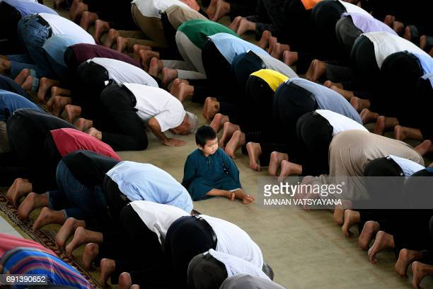 A boy watches as Muslims offer prayers on the first Friday of the holy month of Ramadan at the Tuanku Mizan Zainal Abidin Mosque in Putrajaya on June...