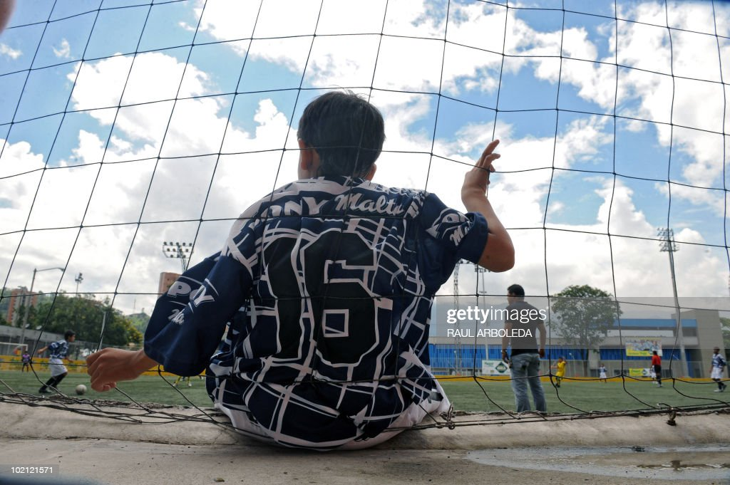 A boy watches as others play during the 'Mundialito' football tournament in Medellin, Antioquia department, Colombia on June 15, 2010. The 'Mundialito' tournament takes place every four years with the participation of Medellin soccer schools. AFP PHOTO/Raul ARBOLEDA