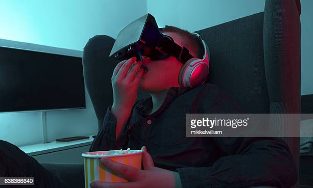 Boy watches movie through virtual reality glasses and eats popcorn