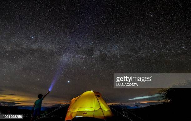 TOPSHOT A boy watches the Milky Way in the sky over the Tatacoa Desert in the department of Huila Colombia on October 11 2018