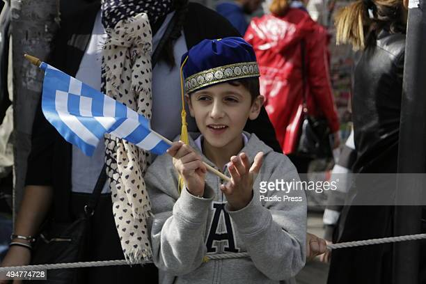 SQUARE ATHENS ATTICA GREECE A boy watches the 'Oxi Day' parade in Athens wearing a traditional hat and waving a Greek flag School students marched in...