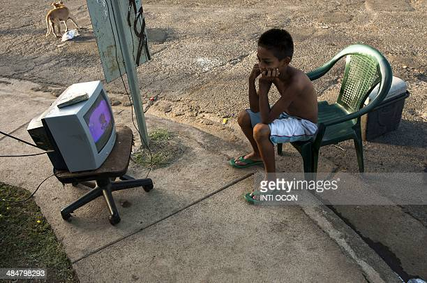 A boy watches TV on a street in Managua on April 14 as tremors have not stopped in Nicaragua since April 10 when a 62magnitude earthquake hit the...