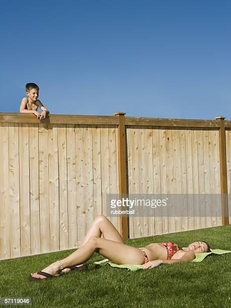 boy watching a woman sunbathe - entrometido fotografías e imágenes de stock