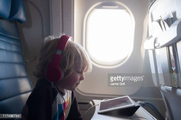 boy watching digital tablet on airplane - arts culture and entertainment stock pictures, royalty-free photos & images
