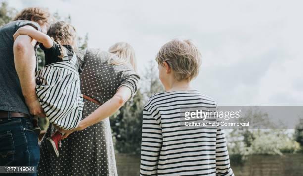 boy watching family - soeur photos et images de collection