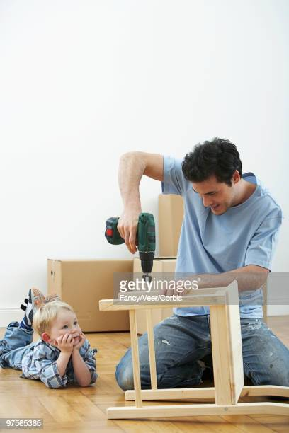 Boy watching father assemble chair
