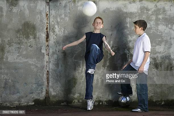 Boy (10-12) watching friend kick football by wall