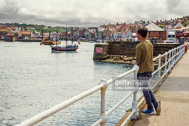 Boy watching harbour scene