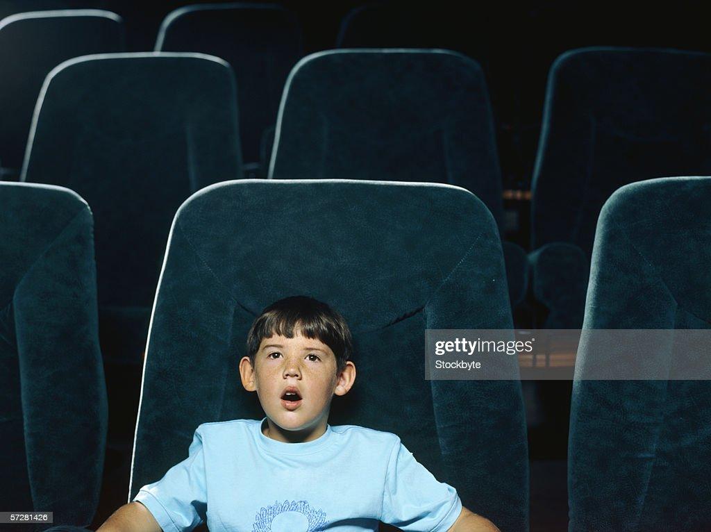 Boy watching movie in a movie theatre : Stock Photo