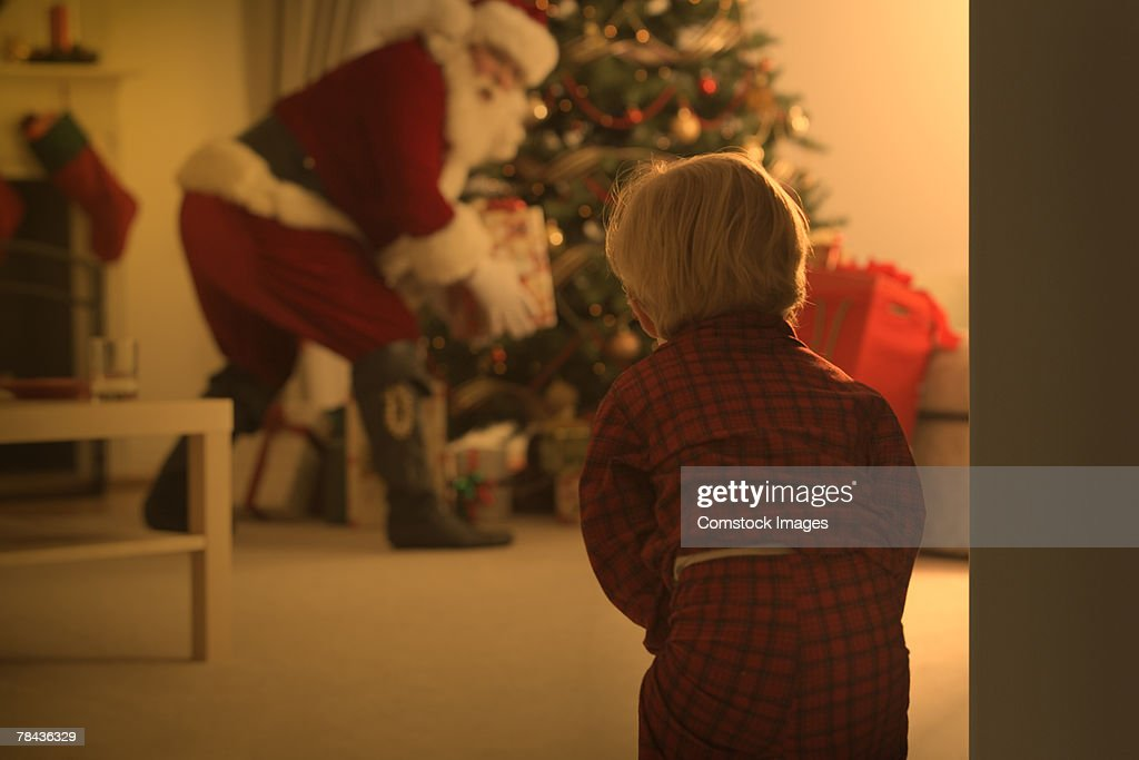 Boy watching Santa put presents under tree : Stockfoto