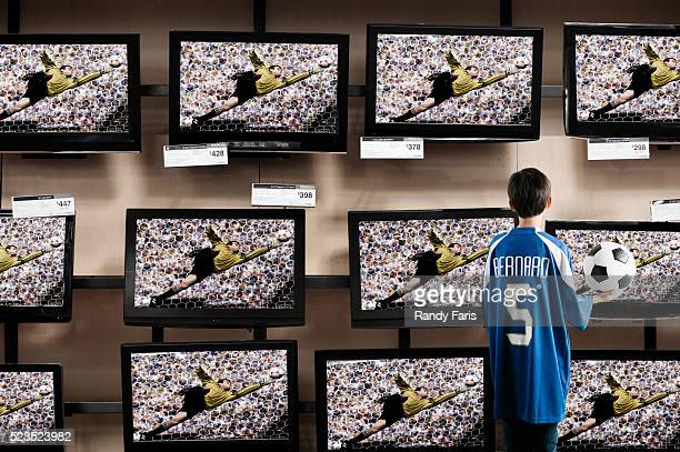 boy watching soccer in a television store - sporting term stock-fotos und bilder