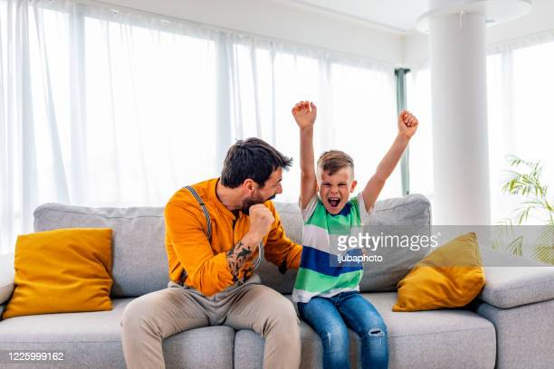 boy watching soccer match with father - match sport stock pictures, royalty-free photos & images