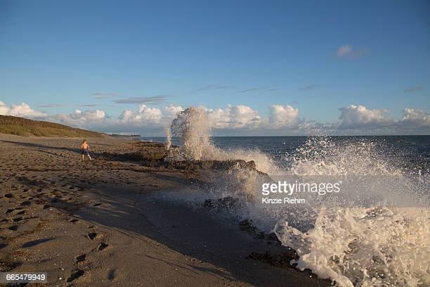 boy watching splashing ocean waves, blowing rocks preserve, jupiter island, florida, usa - jupiter island stock photos and pictures