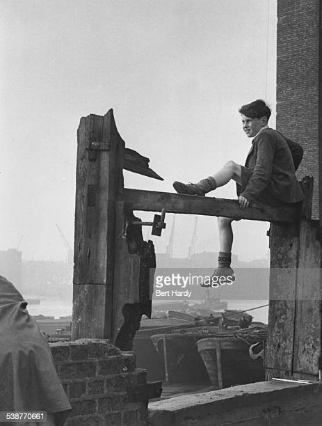 A boy watching the shipping in the Pool of London from the north bank of the Thames at Wapping east London December 1949 Original publication Picture...
