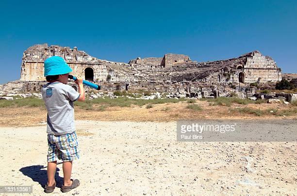 Boy watching through telescope