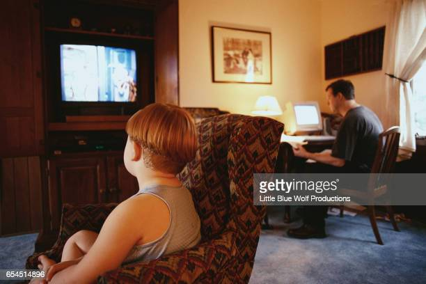 Boy Watching TV While Father Works
