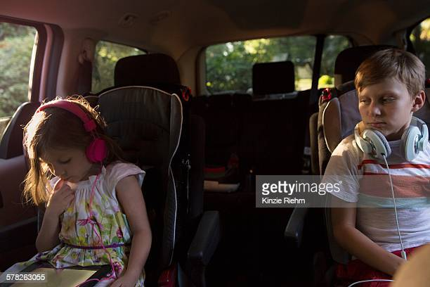Boy watching younger sister using digital tablet in car back seat