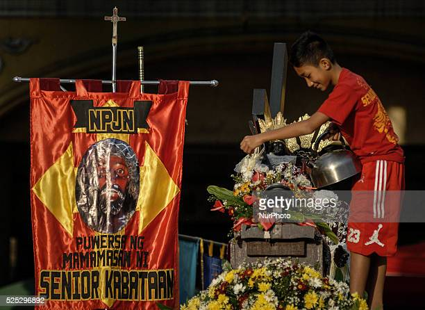 A boy waters flowers adorning a replica of the Black Nazarene outside the Minor Basilica of the Black Nazarene in Manila Philippines January 7 2014...