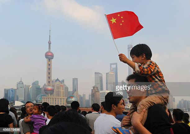A boy waves a Chinese flag riding on his father's neck at the Bund during the second day of the National Day holiday on October 2 2014 in Shanghai...