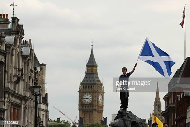 A boy waves a flag as Scotland fans gather in Trafalgar Square ahead of their friendly match against England tonight on August 14 2013 in London...