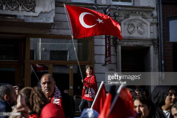 A boy waves a turkish flag as supporters of Turkish President Recep Tayyip Erdogan stand near the new Ditib mosque prior to the arrival of Erdogan on...