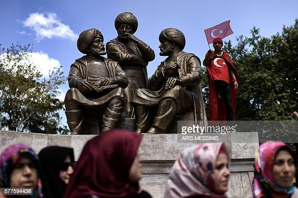 TOPSHOT A boy waves a Turkish flag near Sultan Mehmed II statue during a demonstration in support to the Turkish President at the Sarachane park in...