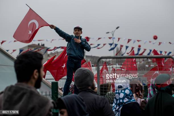 A boy waves a Turkish flag while attending a 'Yes' referendum campaign rally event attended by Turkish President Recep Tayyip Erdogan on March 11...