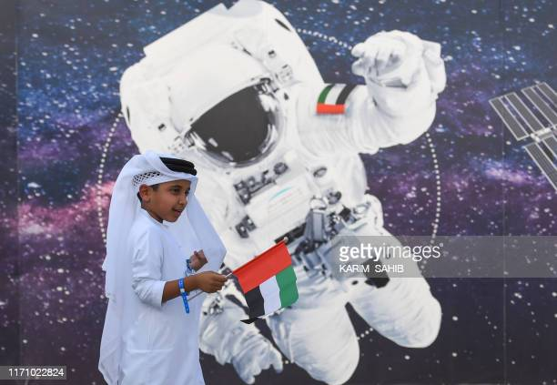 A boy waves the Emirati national flag in front of an illustration depicting an astronaut outside Mohammed Bin Rashid Space Centre in Dubai on...