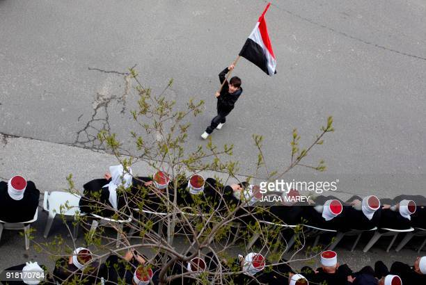 A boy waves the Syrian flag past Druze residents of the Golan Heights during rally in the Druze village of Majdal Shams on February 14 2018 to...