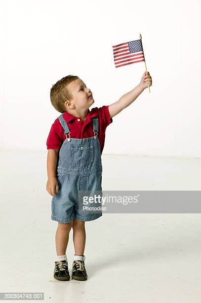 boy (3-4), waving american flag in studio, portrait - alleen jongens stockfoto's en -beelden
