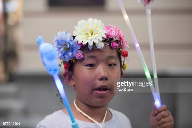 A boy wear a wreath at central street to celebrate upcoming Duanwu Festival in Harbin city of China on June 172018The Dragon Boat Festival also named...