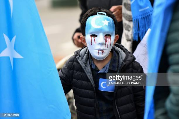 A boy wearing a blue mask with tears of blood takes part in a protest march of ethnic Uighurs asking for the European Union to call upon China to...