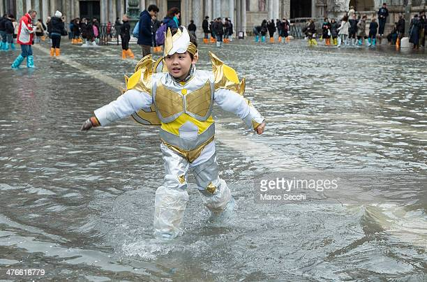 A boy wearing a carnival costume runs in high water in Saint Mark's Square on the last day of Carnival on March 4 2014 in Venice Italy It is the last...