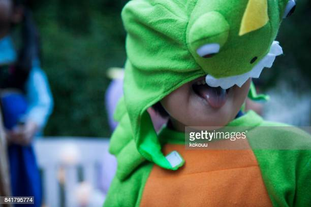 a boy wearing a dinosaur to mischief outside. - naughty halloween stock photos and pictures
