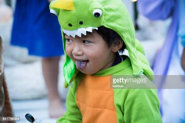Ein Junge, einen Dinosaurier sein Unwesen außerhalb tragen.