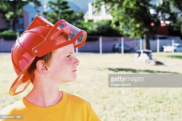 Boy wearing a fireman helmet