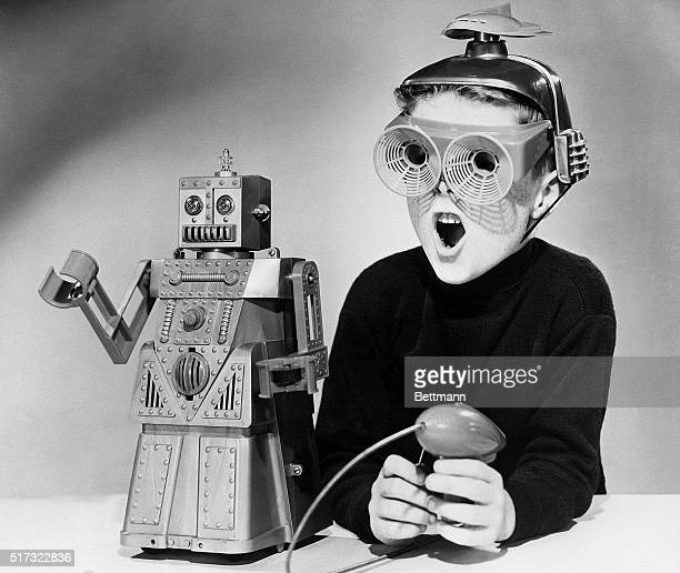Boy wearing a futuristic space helmet and goggles demonstrates the wonders of Robert the Robot, a new toy manufactured by the Ideal Toy Corp. The...
