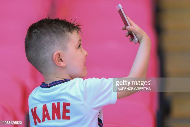 Boy wearing a jersey of England's forward Harry Kane uses a smartphone before the start of the UEFA EURO 2020 Group D football match between England...
