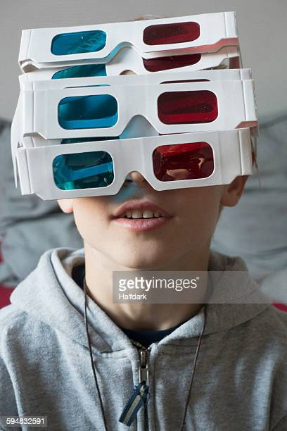 A boy wearing a large amount of 3-D glasses