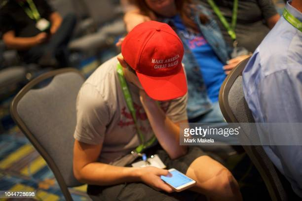 A boy wearing a MAKE AMERICA GREAT AGAIN hat uses a smartphone before US President Donald Trump addresses the National Electrical Contractors...