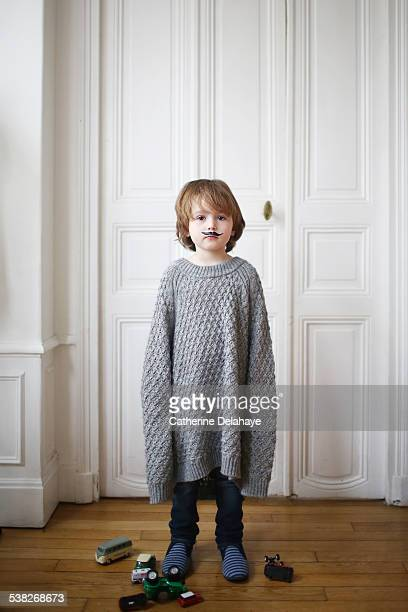 A boy wearing a moustache and a too long sweater