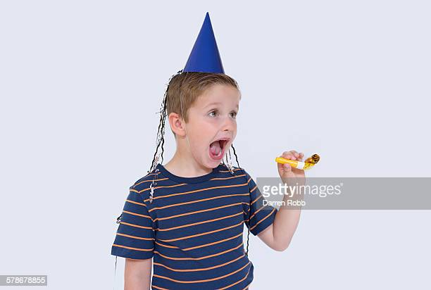 Boy wearing a party hat screaming with excitement
