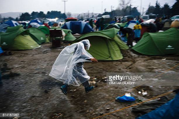 TOPSHOT A boy wearing a plastic rain cover runs among tents at a makeshift camp of the GreekMacedonian border near the Greek village of Idomeni on...