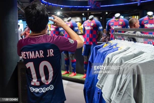 A boy wearing a PSG jersey bearing the name of Brazilian forward Neymar Jr takes pictures at the official Barcelona FC store in Barcelona on August 2...