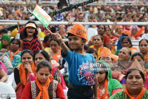 A boy wearing a saffron cap attends a Bhartiya janta Party rally as Indian Prime Minister Narendra Modi speaks at Surendranagar some 130 kms from...