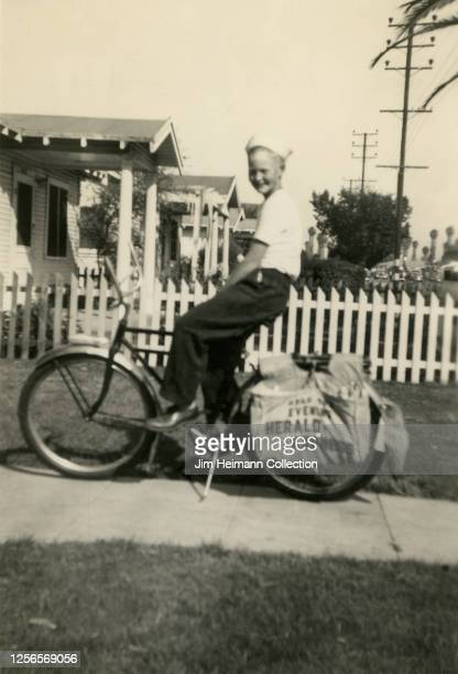 A boy wearing a sailor cap sits on a bicycle with an Evening HeraldExpress newspaper delivery bag strapped to its back wheels circa 1940