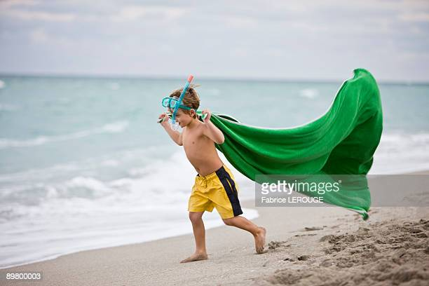 Boy wearing a scuba mask and running on the beach
