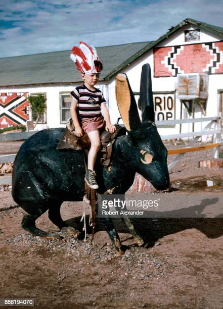 A boy wearing a souvenir Indian headdress sits on a giant cement rabbit at the Jack Rabbit Trading Post on Route 66 near Joseph City Arizona The...