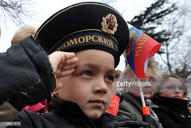 A boy wearing a Soviet era sailor's cap salutes on May 9 2011 during a Victory Day celebrations in Sevastopol in commemoration of the end of World...